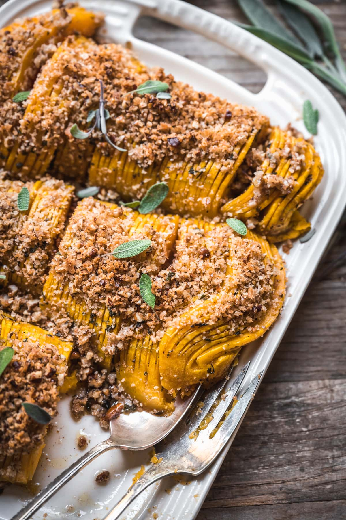 close up view of vegan hasselback butternut squash with breadcrumbs.