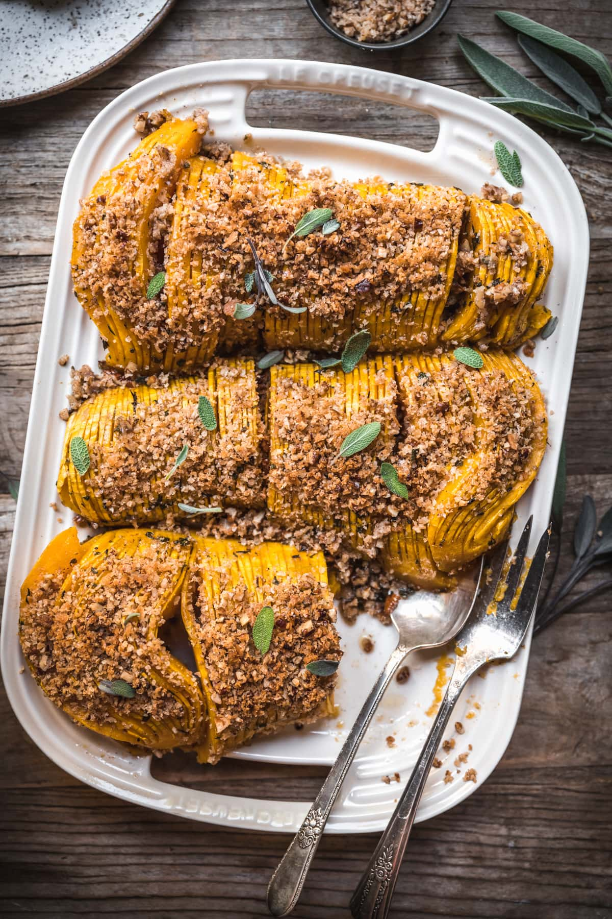 overhead view of hasselback butternut squash with breadcrumbs on a white platter with serving utensils.