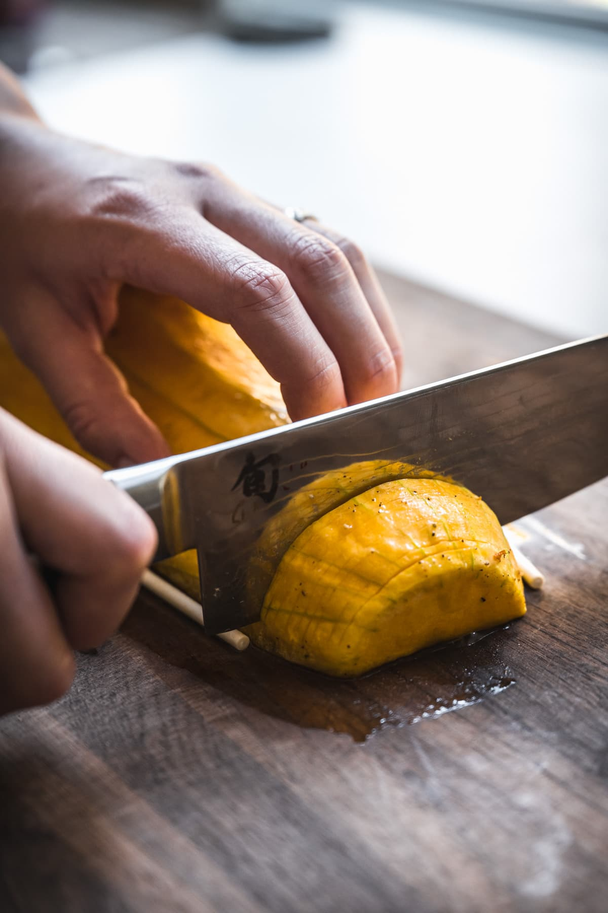 person slicing into a butternut squash with a large knife on a cutting board.