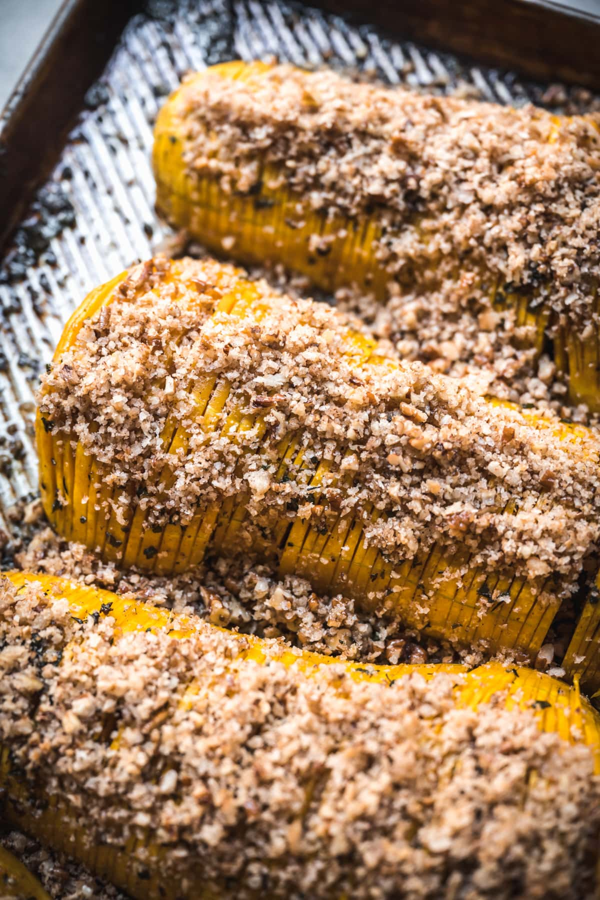 close up view of hasselback butternut squash with breadcrumbs on a sheet pan.