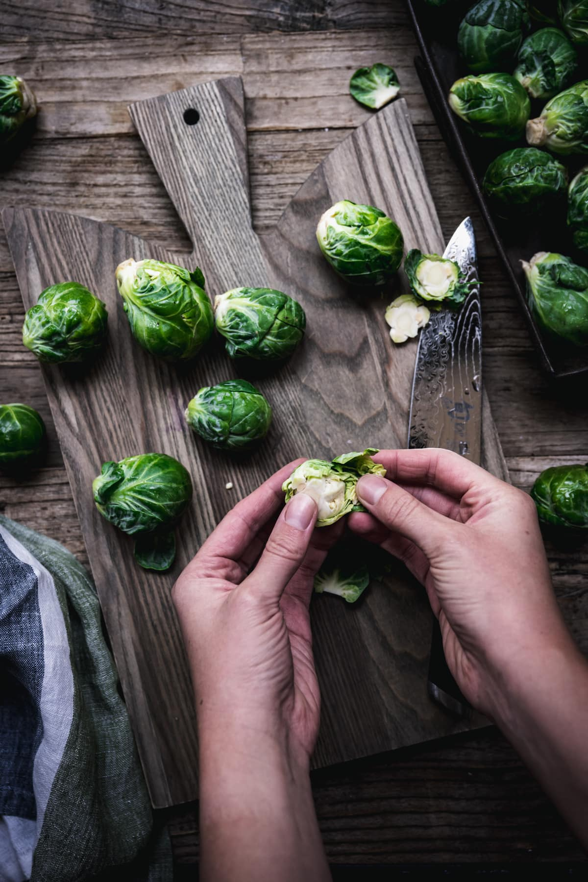 overhead view of person peeling leaves form a brussels sprout.