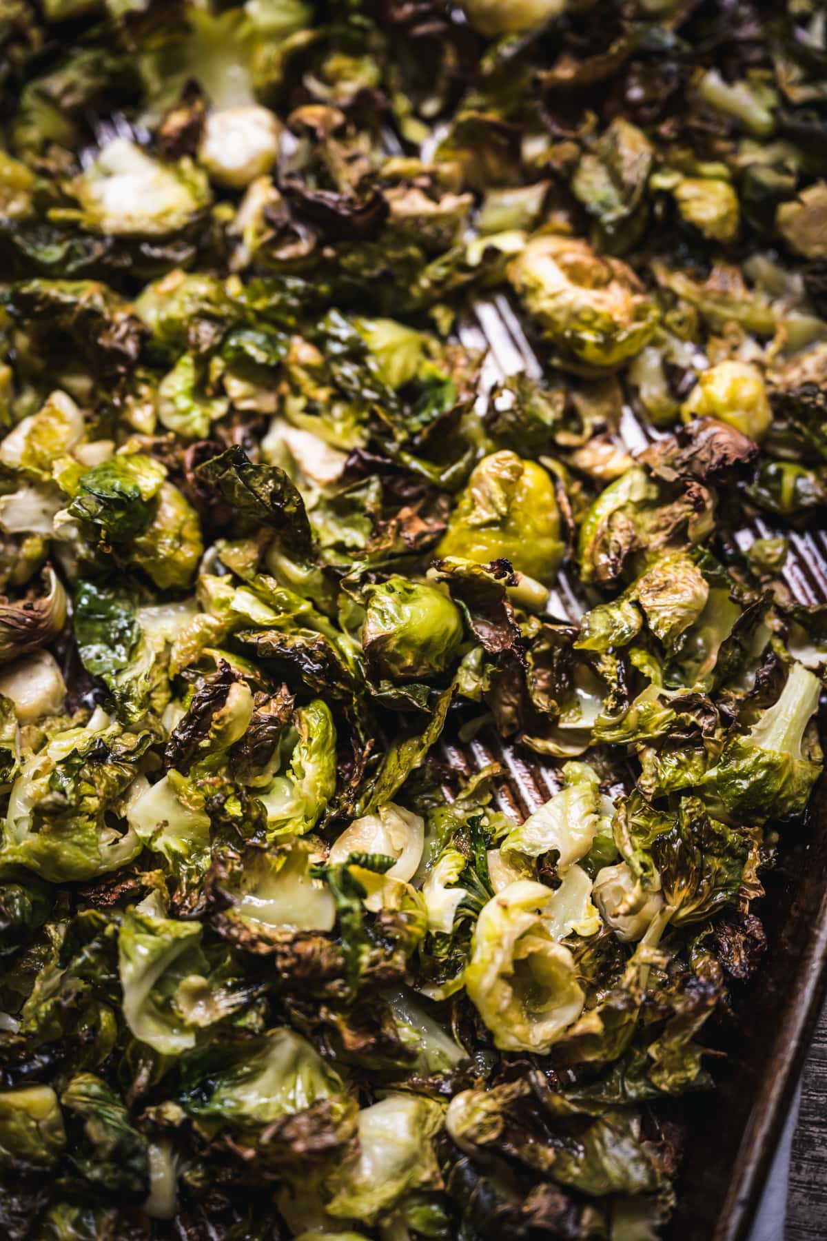 close up view of crispy roasted brussels sprouts on a baking sheet.