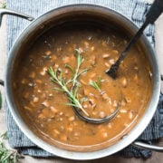 close up overhead view of vegan mushroom gravy in a pot garnished with fresh rosemary.