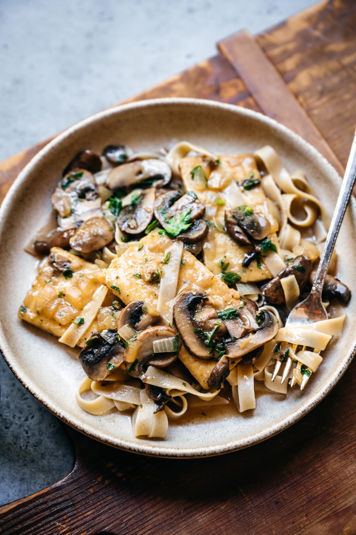 side view of tofu marsala in a bowl with pasta.