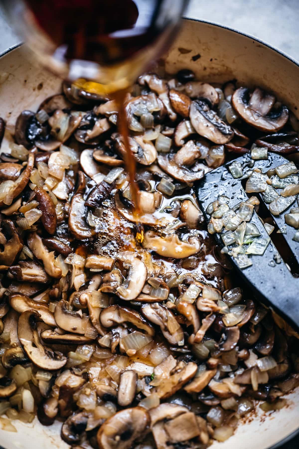 pouring marsala wine into mushroom sauce.