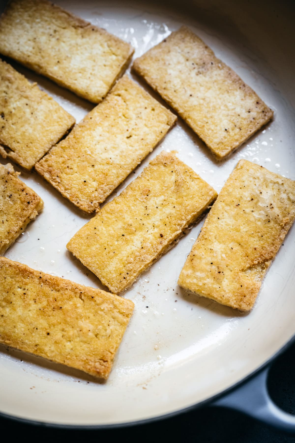 close up view of pan-fried tofu cutlets in a pan.