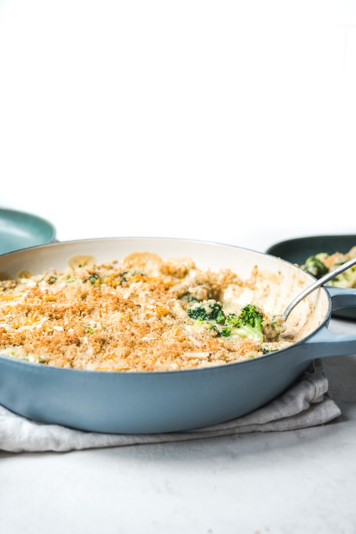 side view of large skillet with vegan broccoli casserole and serving spoon.