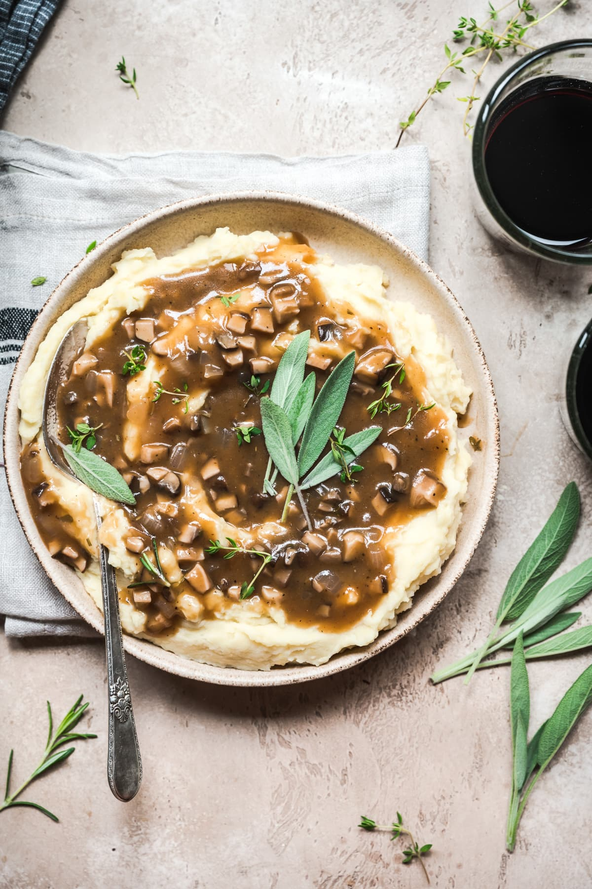 overhead view of bowl of mashed potatoes topped with vegan mushroom gravy and fresh sage.