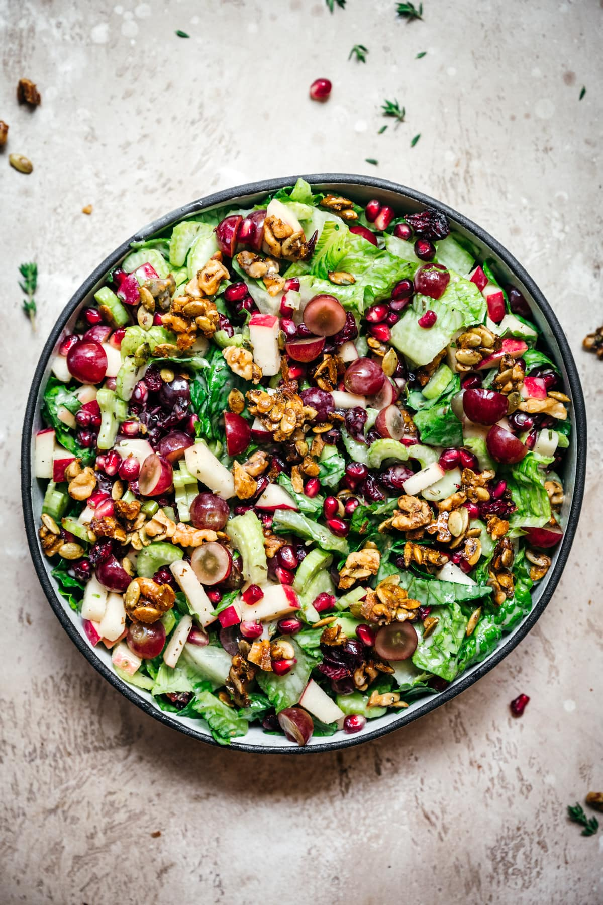 overhead view of vegan waldorf salad with walnut brittle and pomegranate in a bowl.