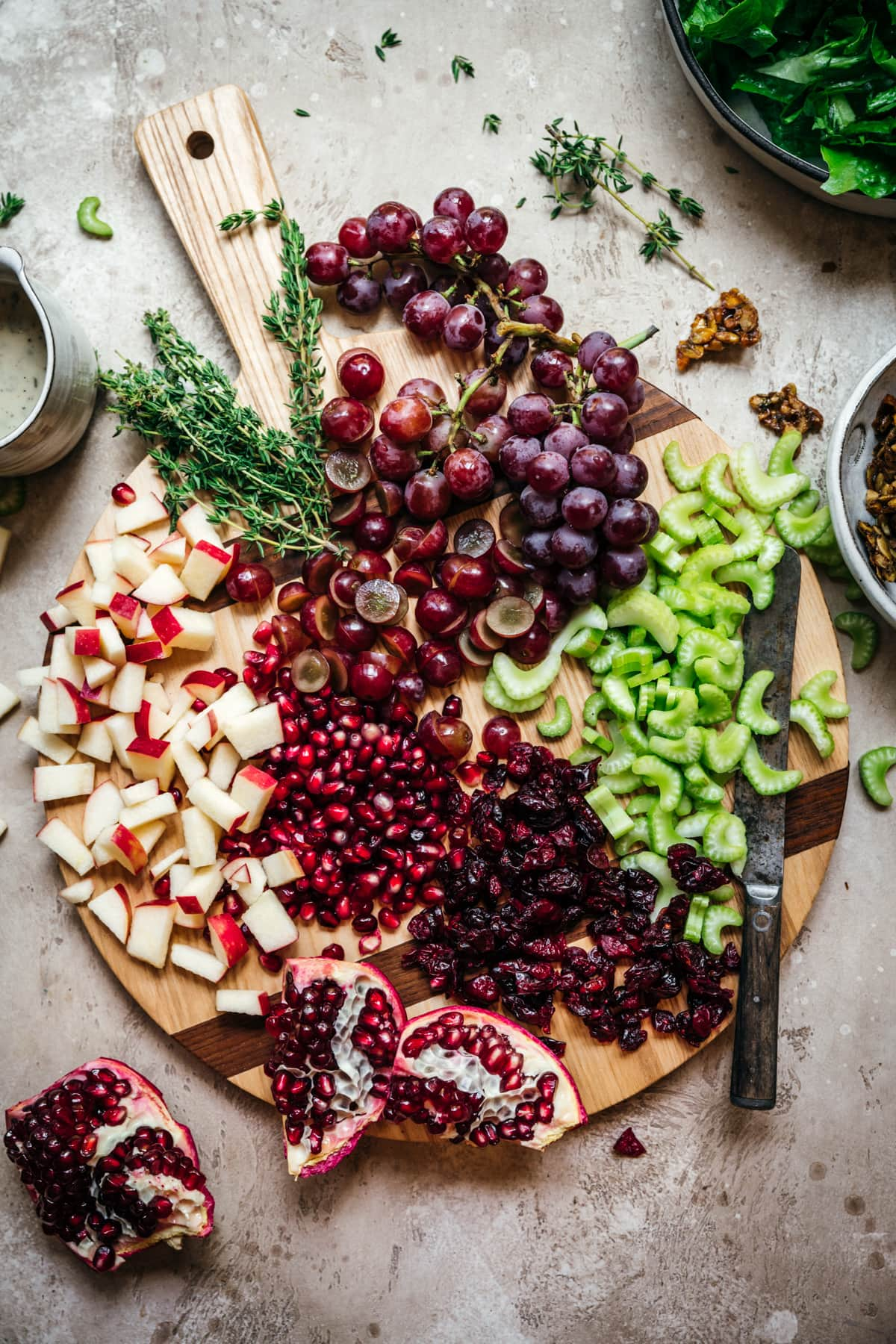 overhead view of ingredients for waldorf salad on a cutting board, including celery, grapes, dried cranberries, apples and pomegranate.