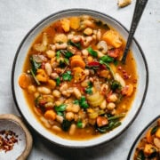 close up overhead view of vegan bean soup in a bowl on white linen surface.