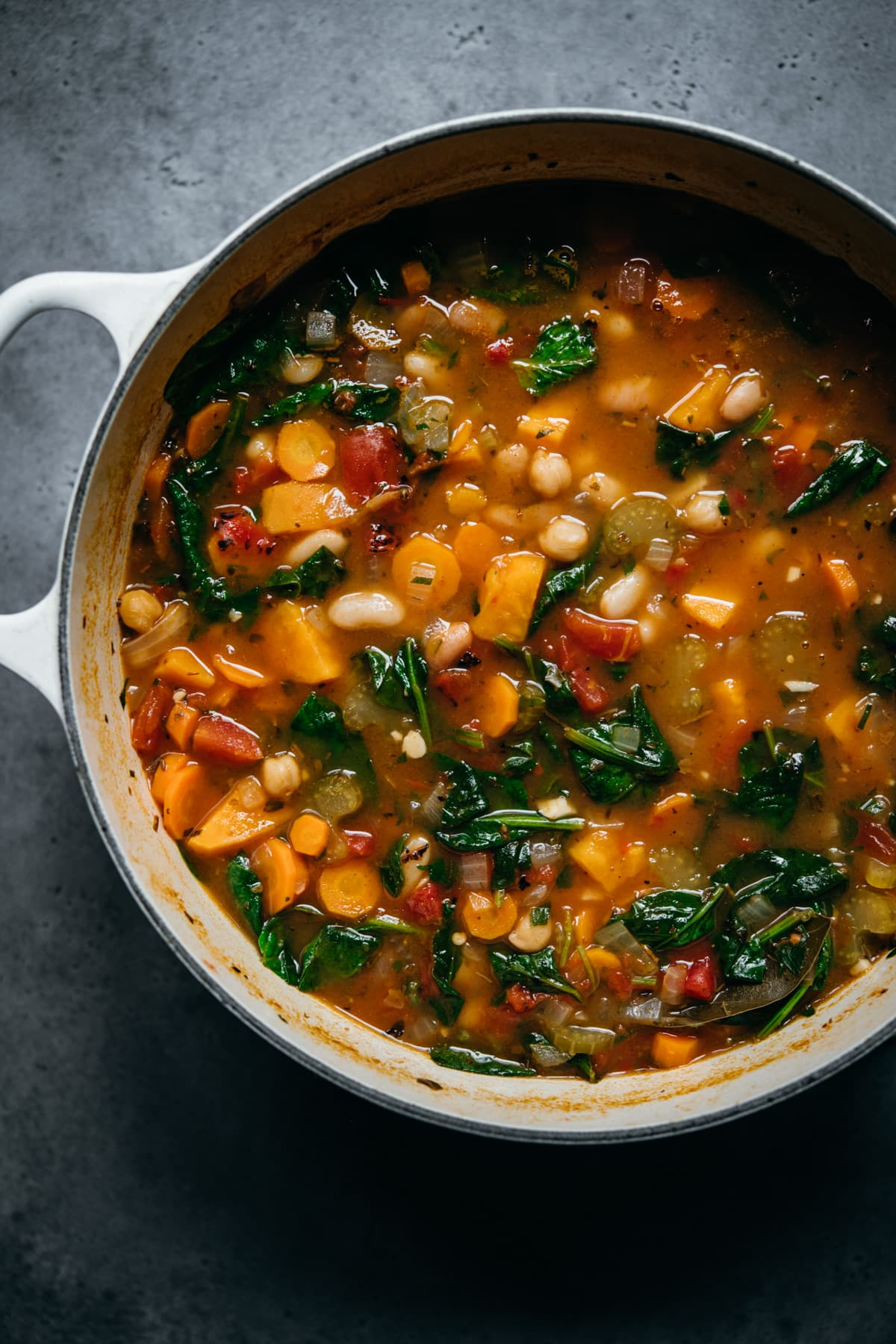 overhead view of vegan bean vegetable soup in white pot.