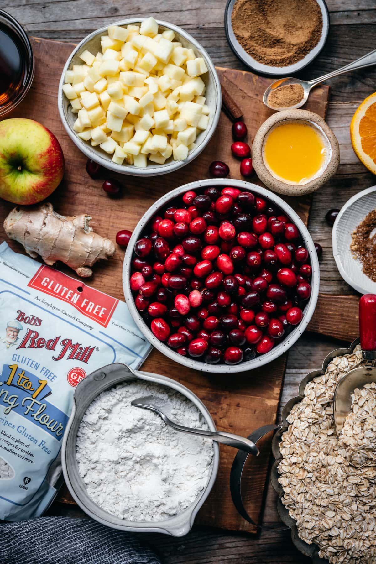 overhead view of ingredients for cranberry crumb bars, including fresh cranberries, apples, orange juice, flour, oats, etc.