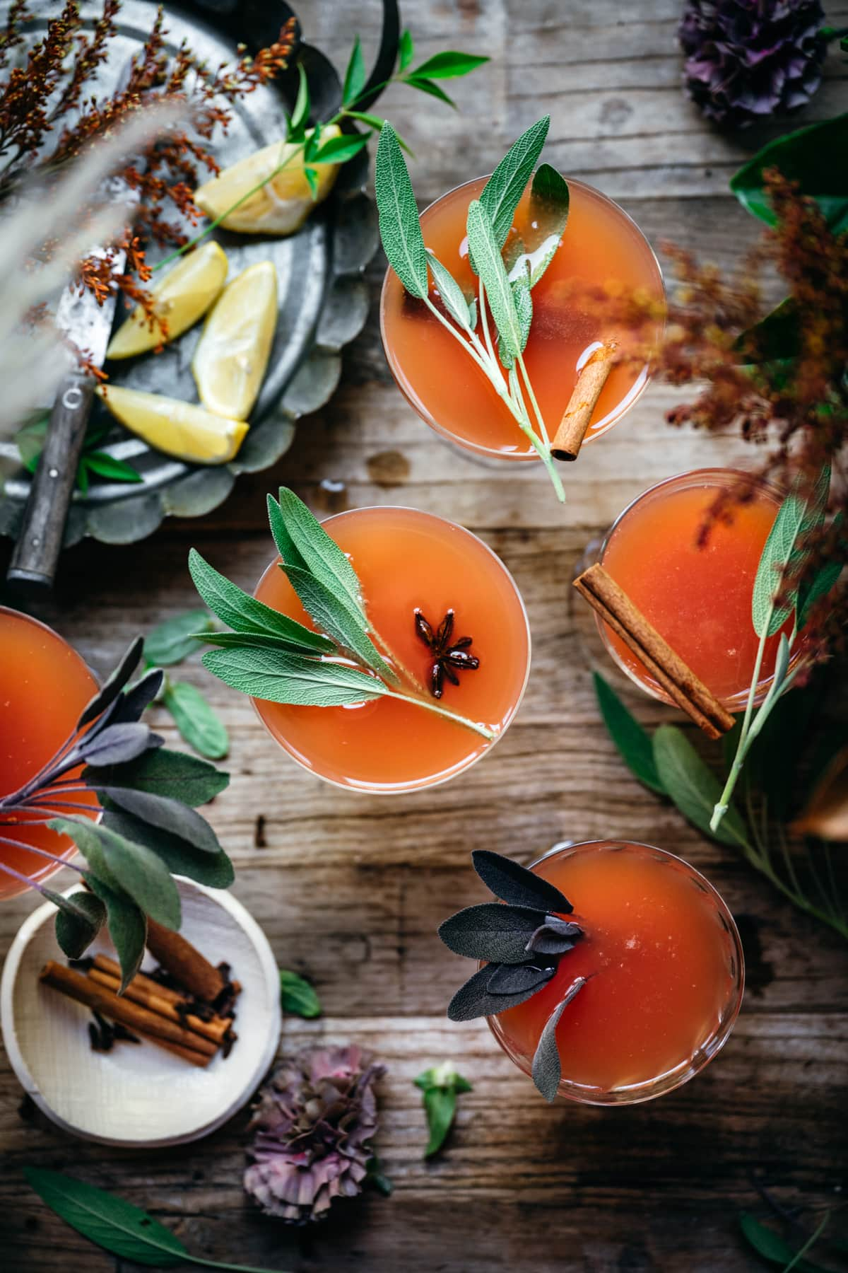 overhead view of cranberry orange mimosas garnished with fresh sage.