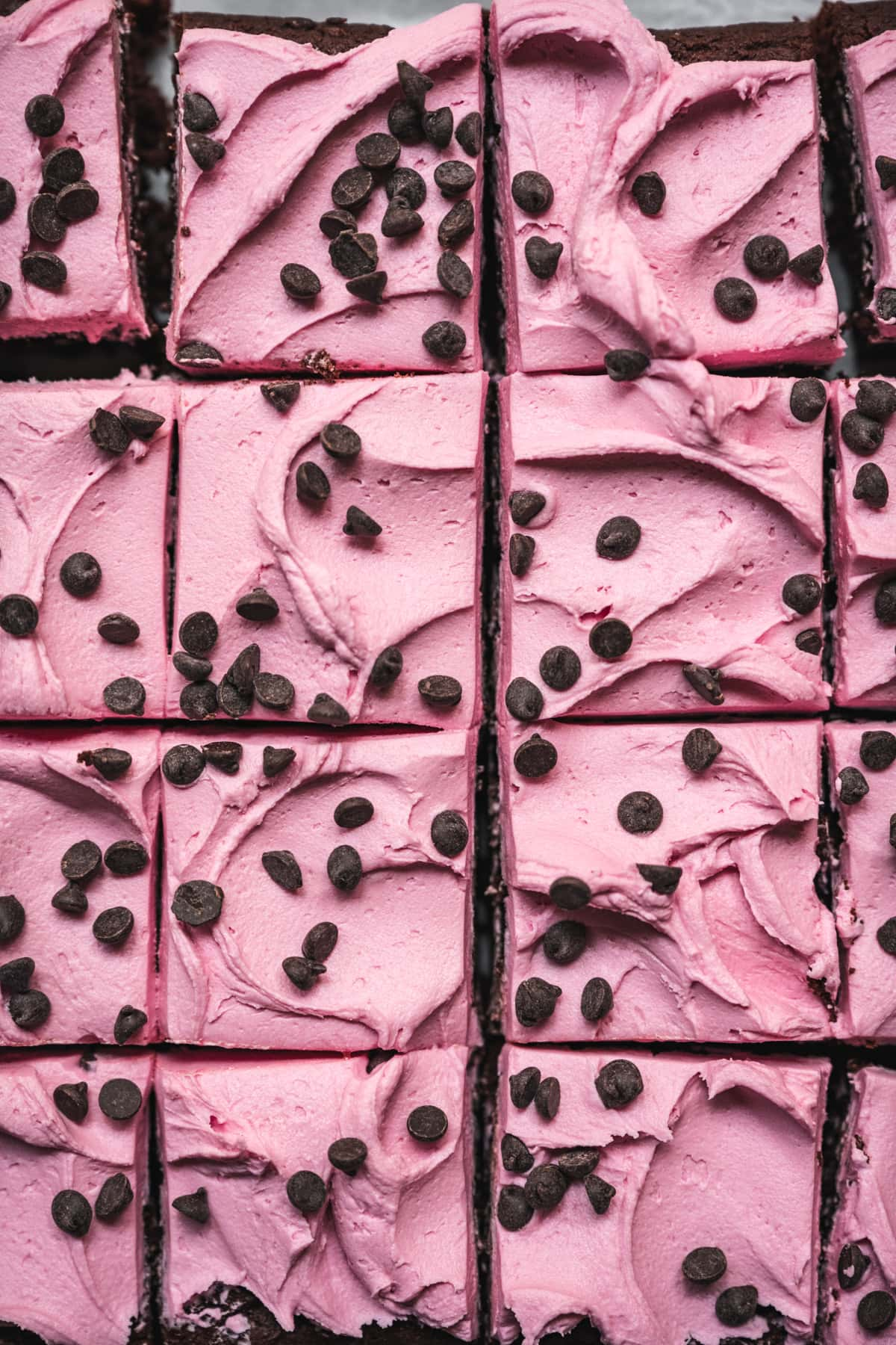 overhead view of beet brownies sliced and topped with pink frosting and chocolate chips.