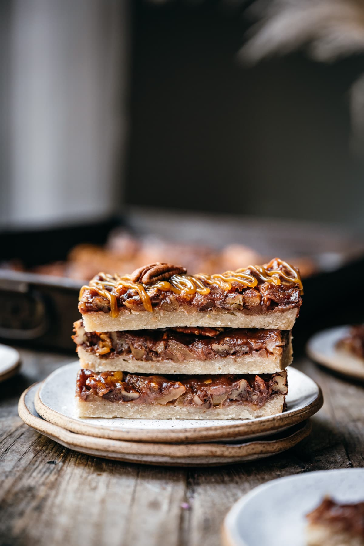 side view of stack of 3 vegan pecan pie bars on small white plate.