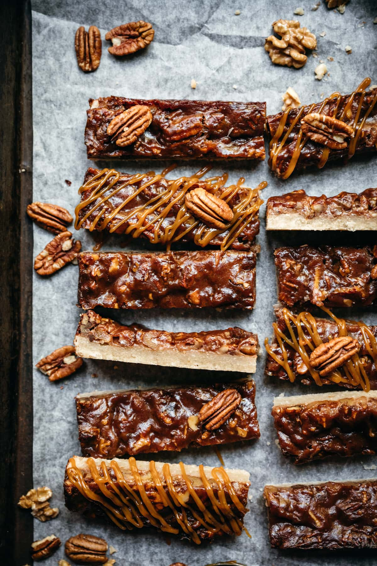 overhead view of maple bourbon pecan pie bars sliced on parchment paper.