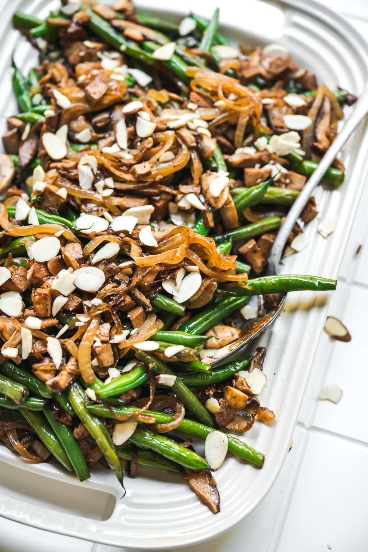 close up side view of vegan green beans with tofu bacon, mushrooms and caramelized onions on white platter.