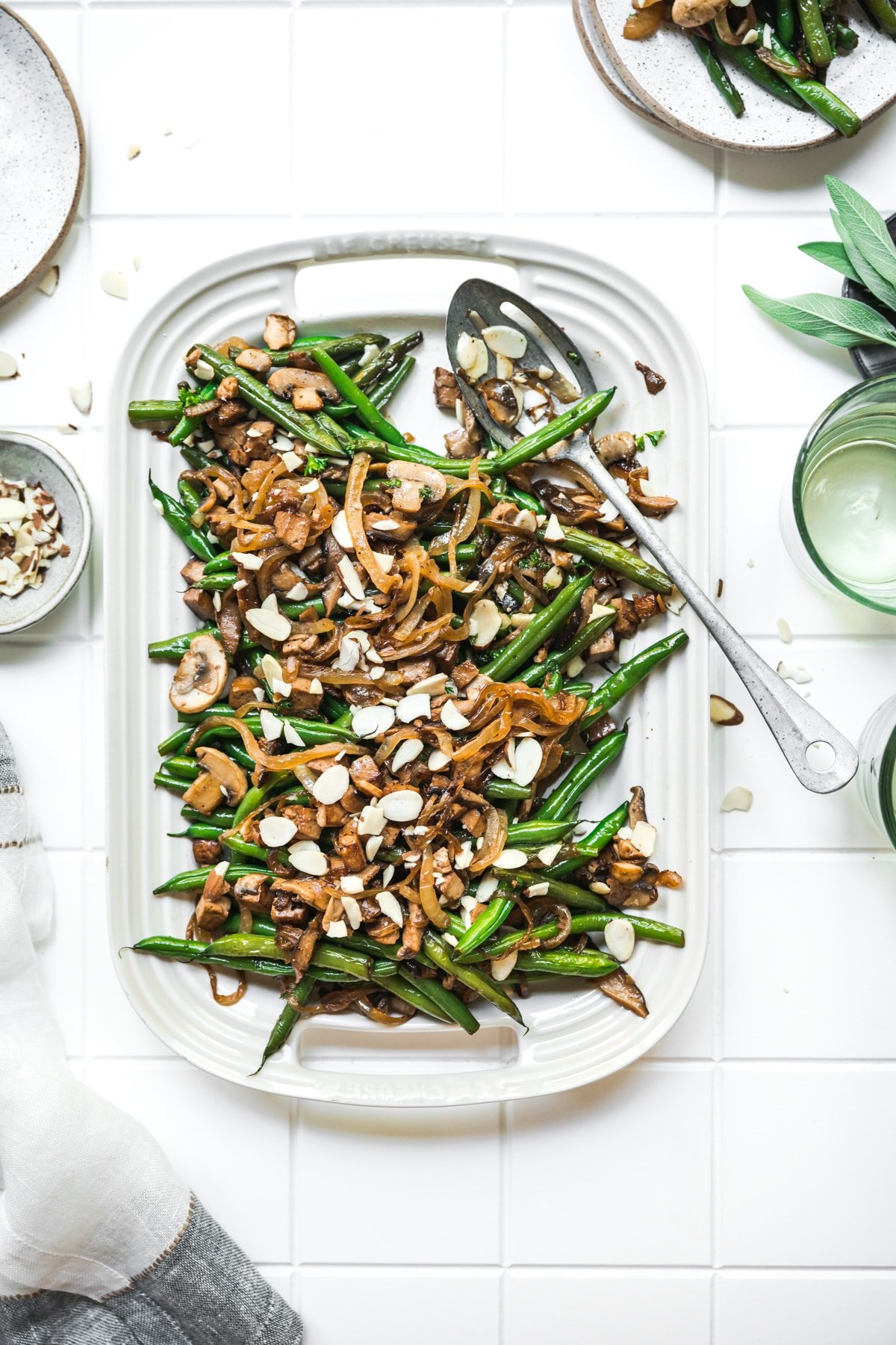 overhead view of vegan green beans with tofu bacon, mushrooms and caramelized onions on white platter.