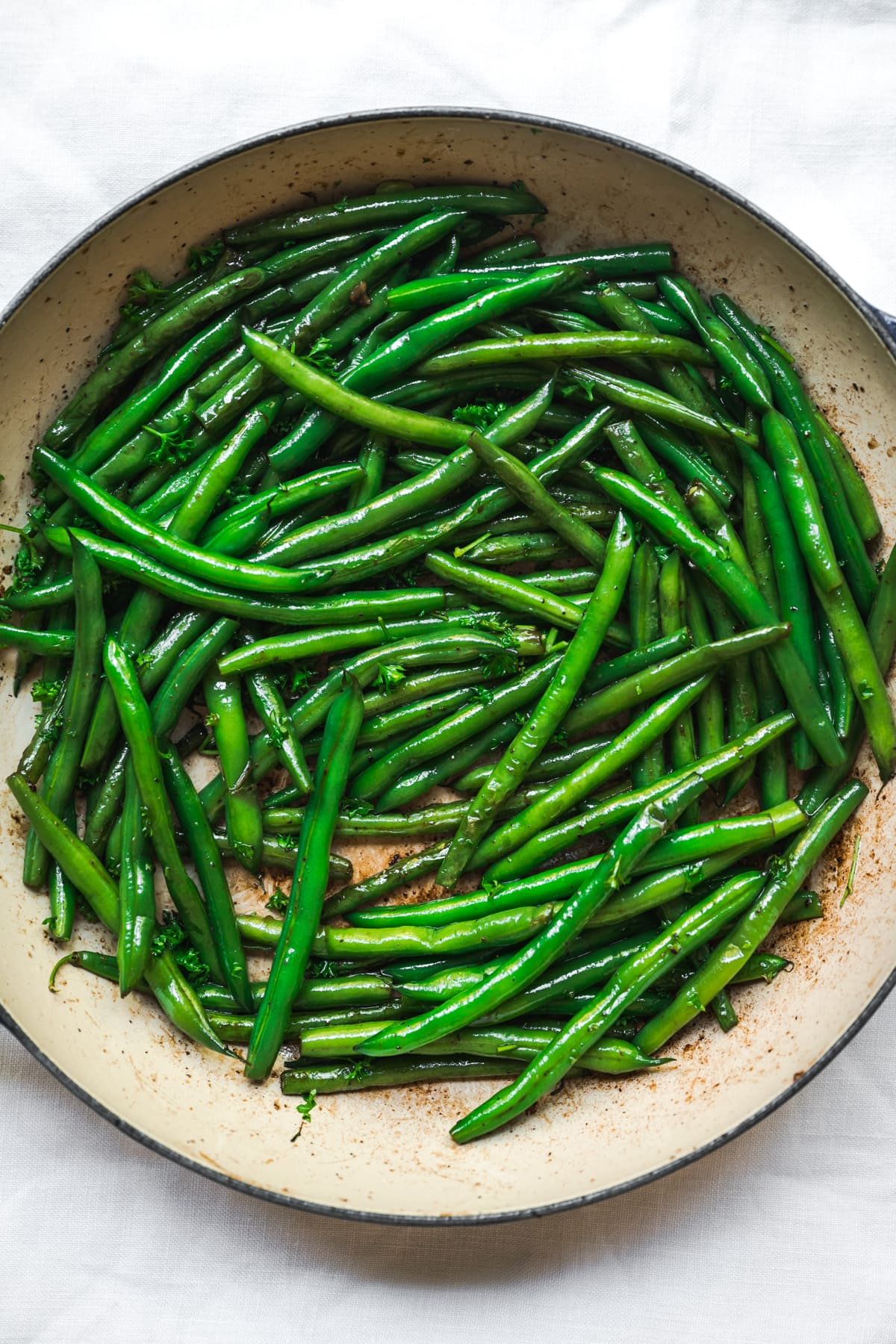 overhead view of sautéed green beans in a pan.