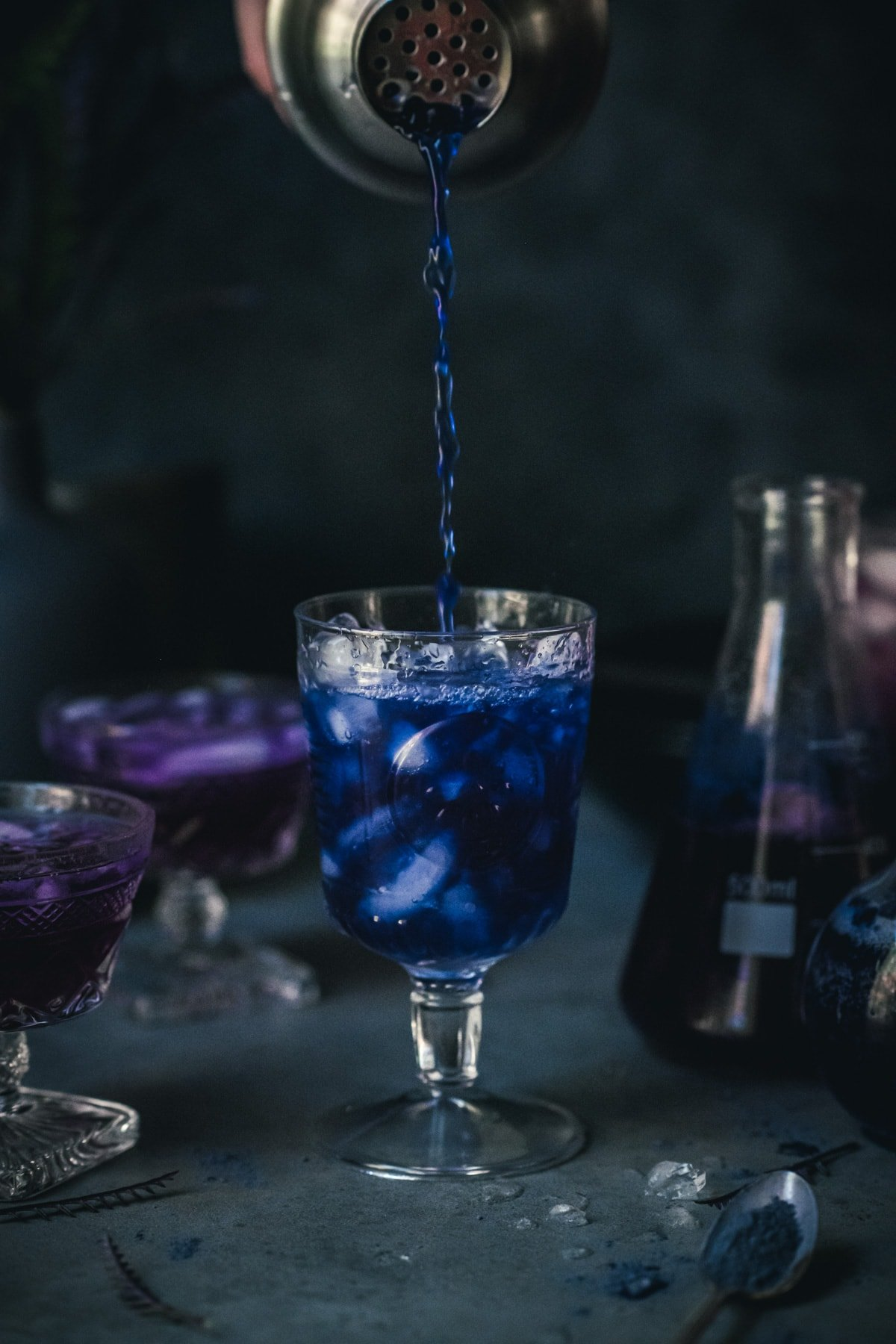 pouring blue butterfly pea tea into a cocktail glass