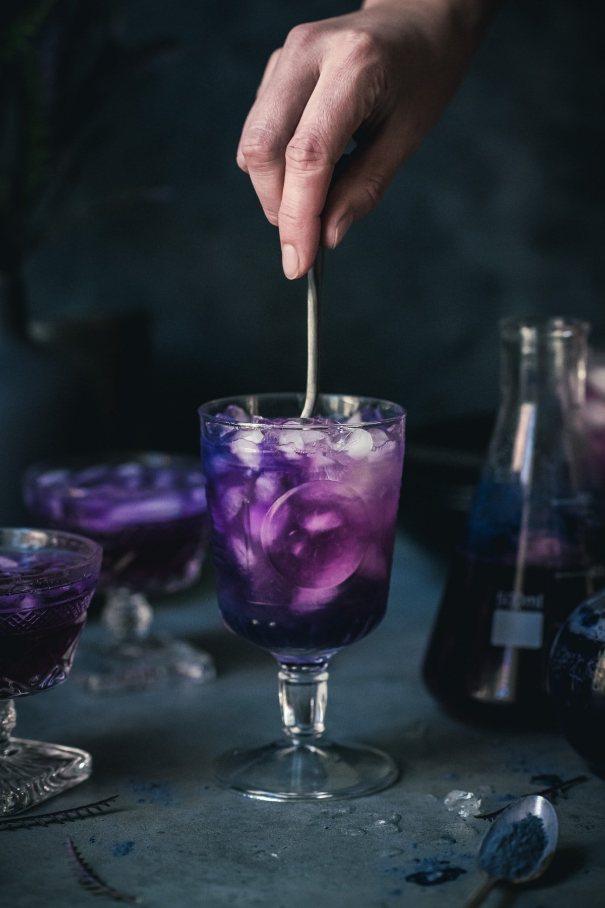person stirring a purple halloween cocktail in a goblet glass.