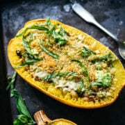 close up side view of spaghetti squash filled with pesto, white beans and topped with breadcrumbs.