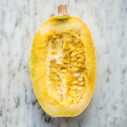 overhead view of spaghetti squash sliced in half on marble surface.