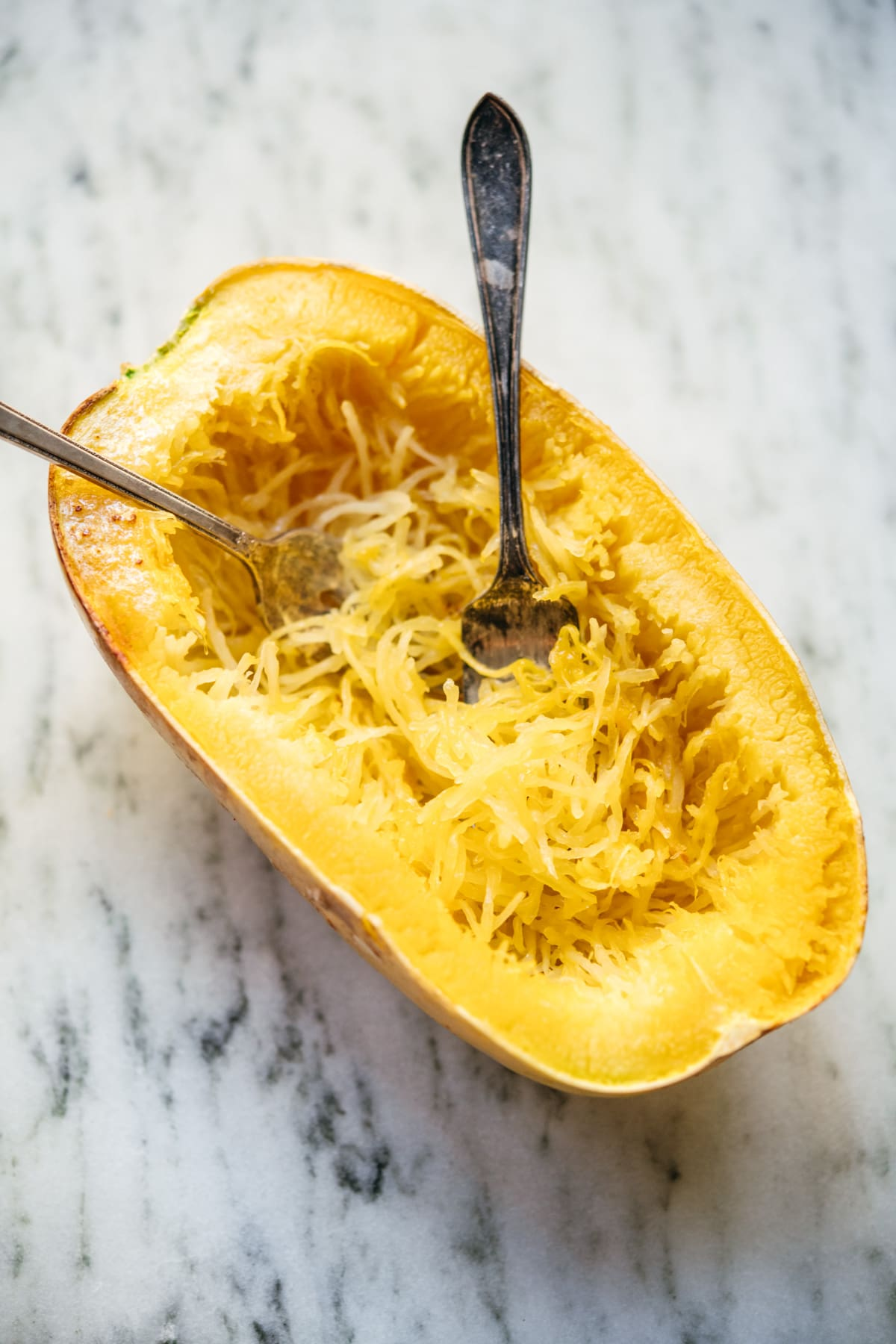side view of two forks in a cooked, shredded spaghetti squash.