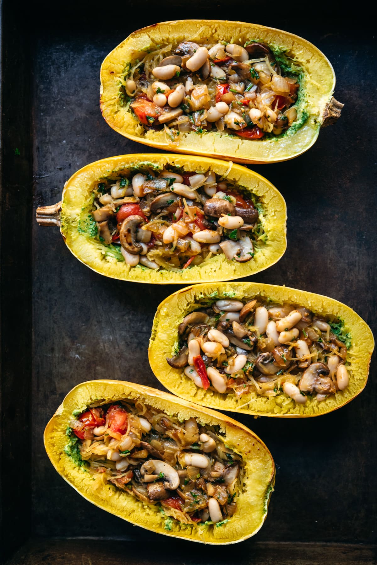 Four spaghetti squash filled with white beans, mushrooms and tomatoes.