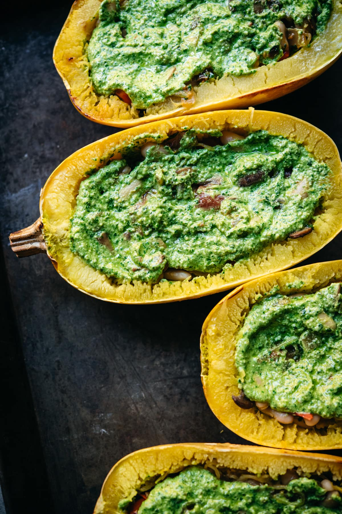 close up of spaghetti squash with mushroom filling and pesto on top.