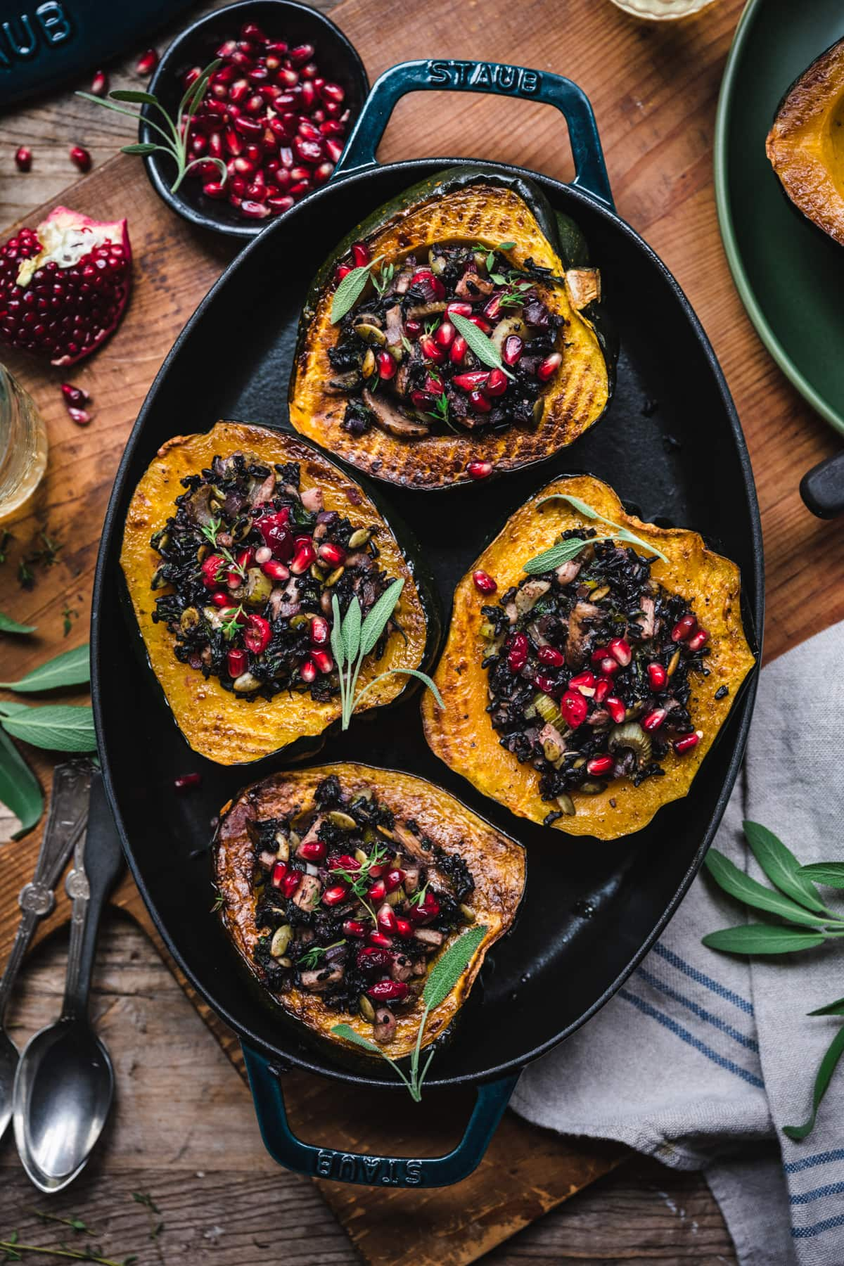 overhead view of vegan stuffed acorn squash with black rice, mushrooms and pomegranate seeds on top.