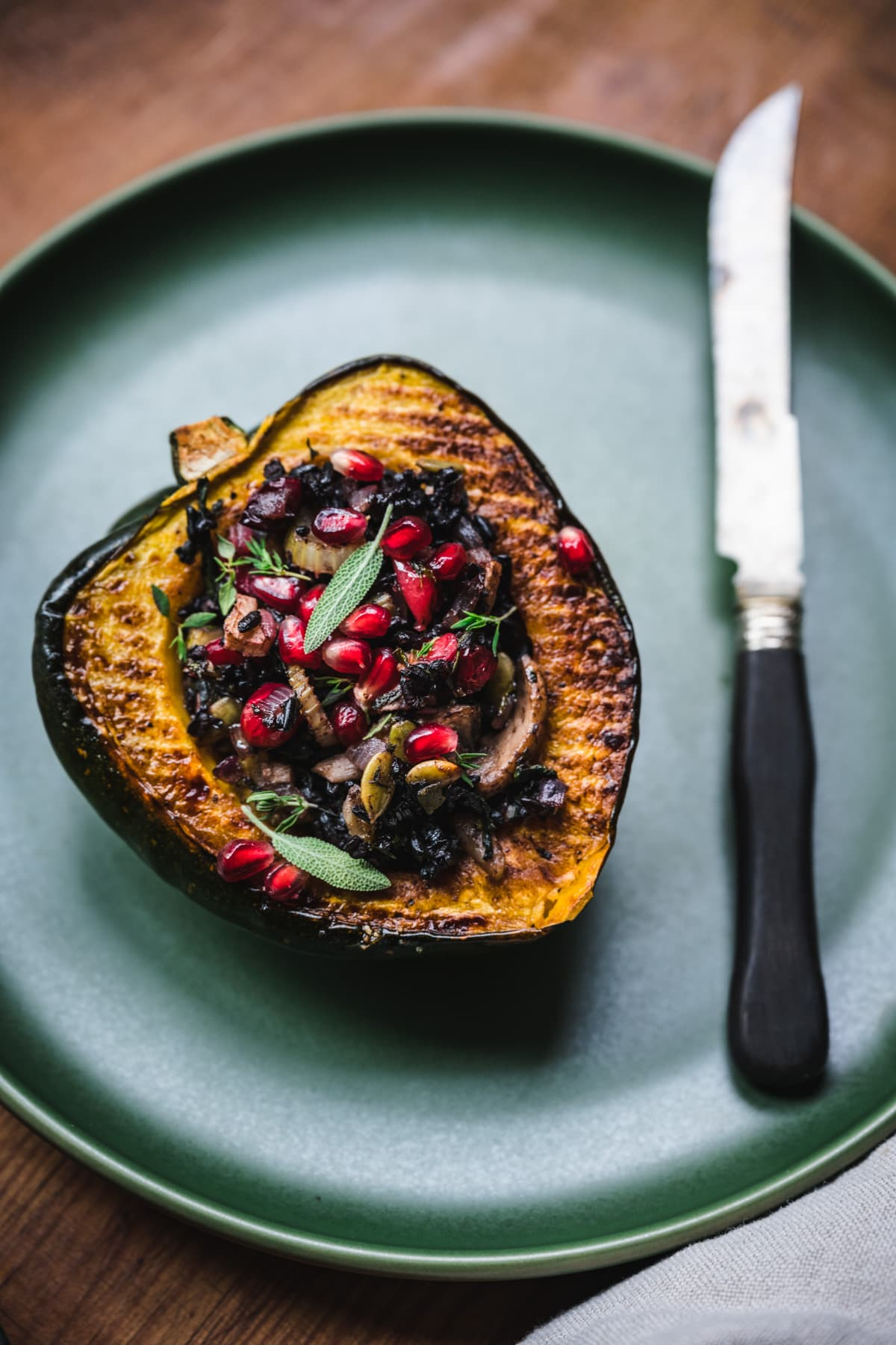 side view of vegan stuffed acorn squash with black rice, mushrooms and pomegranate seeds on top.