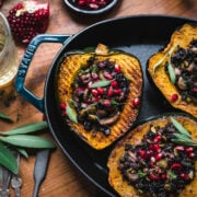 overhead view of slices of vegan stuffed acorn squash with black rice, mushrooms and pomegranate seeds on top.