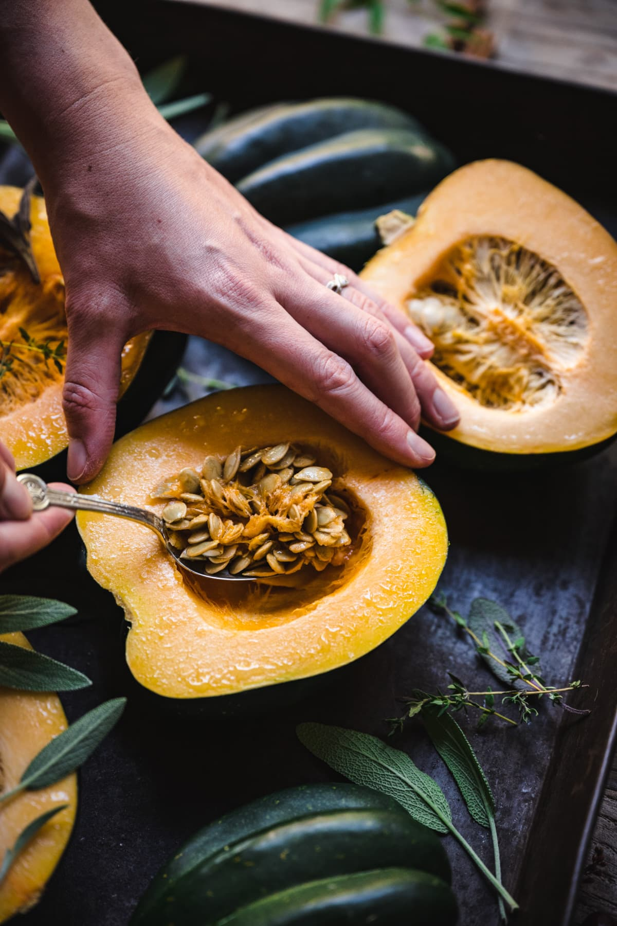 scooping seeds out of a half of an acorn squash.
