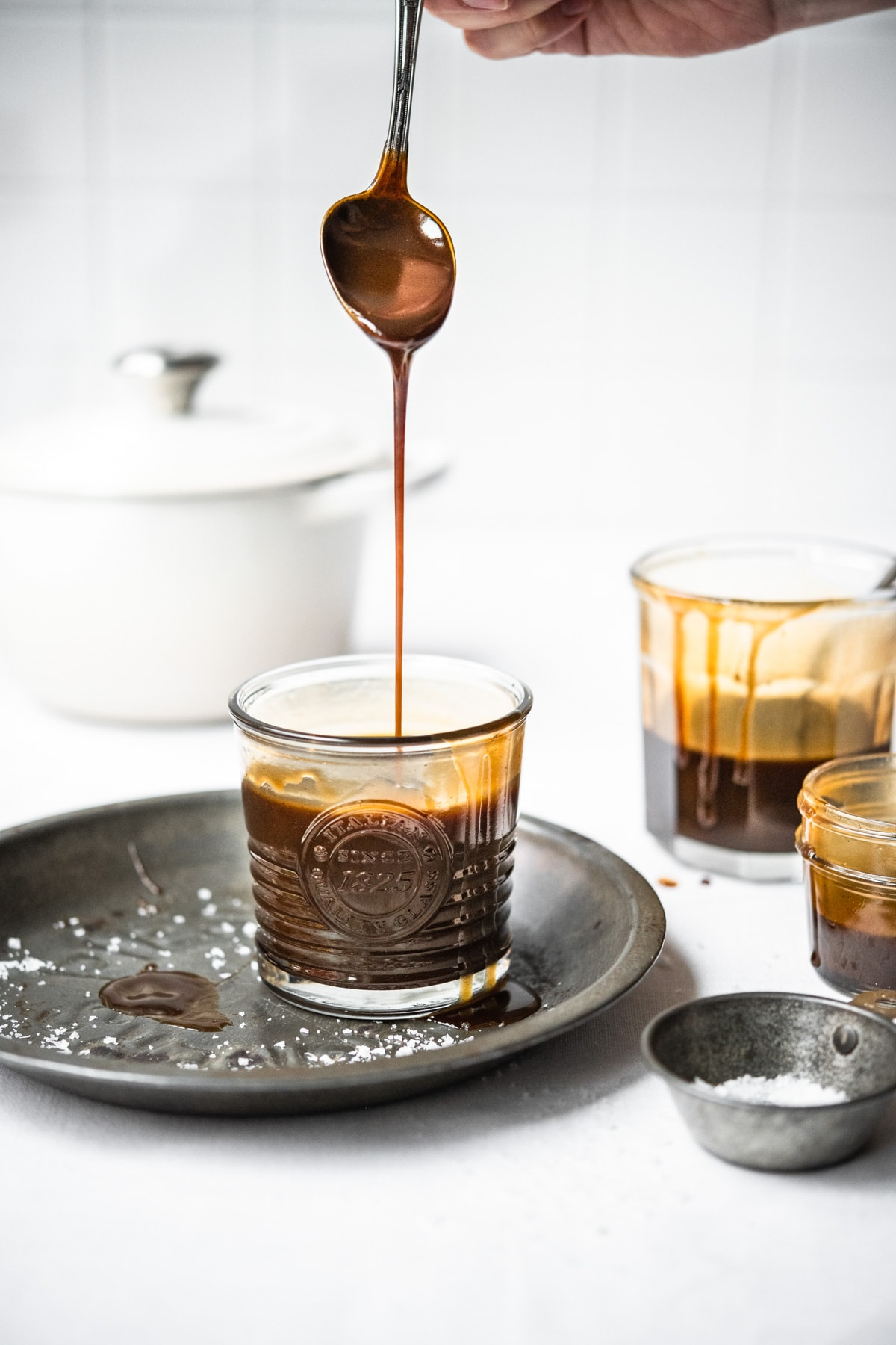 side view of person drizzling caramel sauce into a jar.