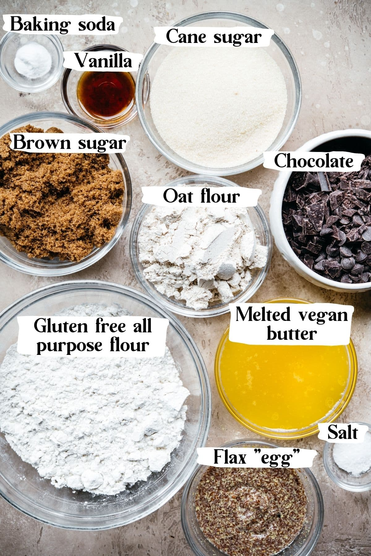 overhead view of ingredients in glass bowls to make vegan chocolate chip cookies with text labels on photo.