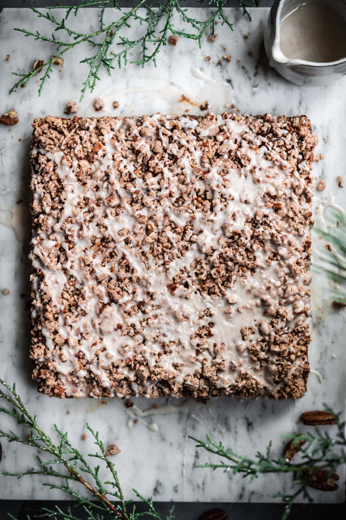 close up overhead view of gingerbread coffee cake with pecan streusel and vanilla glaze.