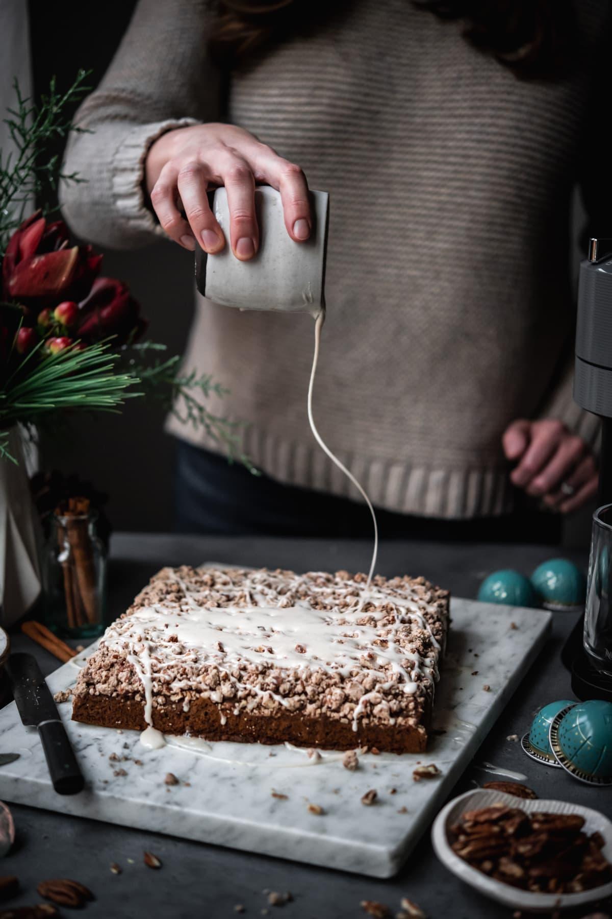 person drizzling vanilla glaze onto coffee cake.