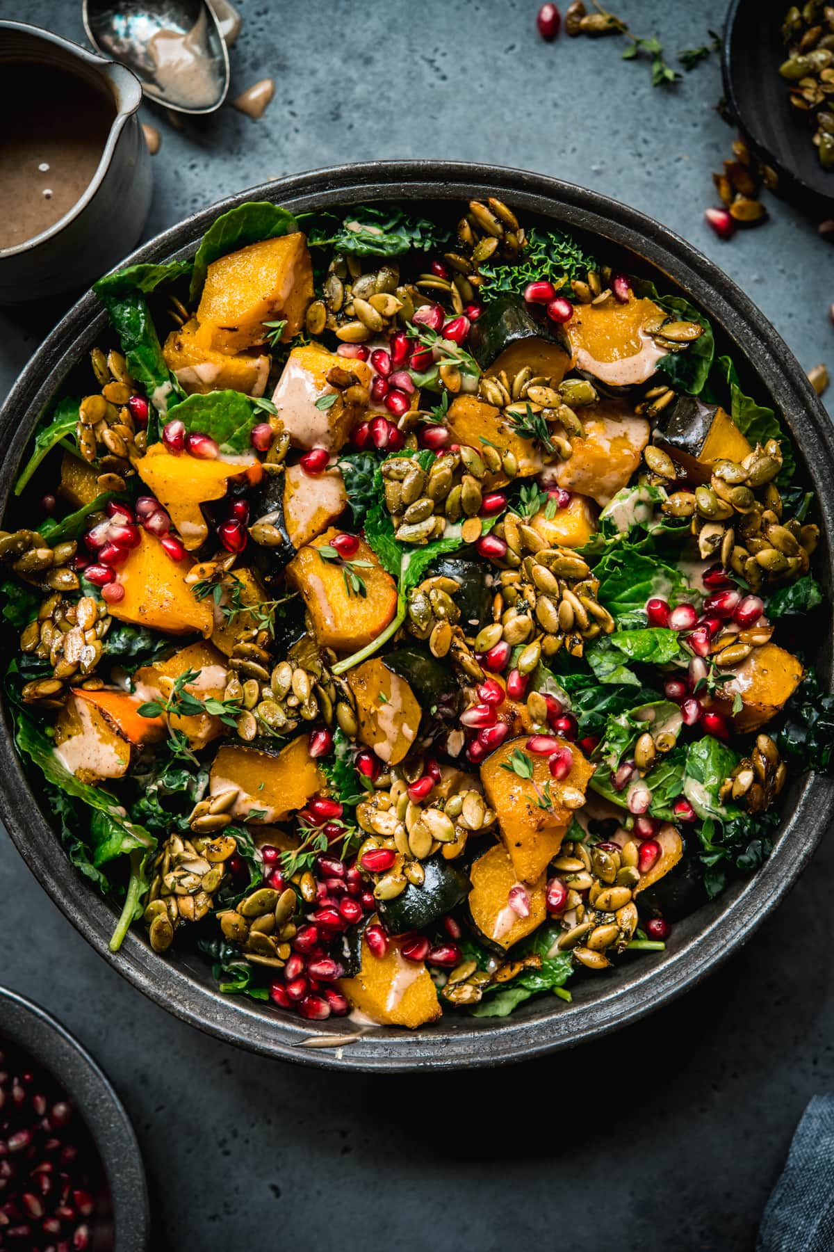 overhead view of roasted acorn squash salad with pumpkin seed brittle and pomegranate.