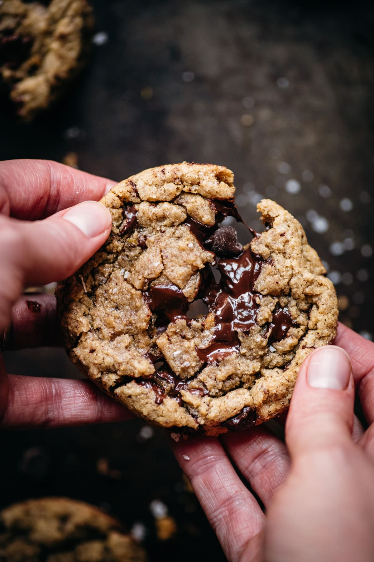 close up view of two hands pulling apart a freshly baked chocolate chip cookie.