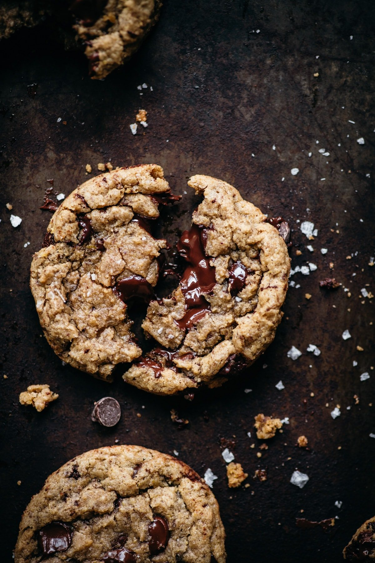 close up overhead view of melty vegan chocolate chip cookie broken in half on rustic sheet pan.