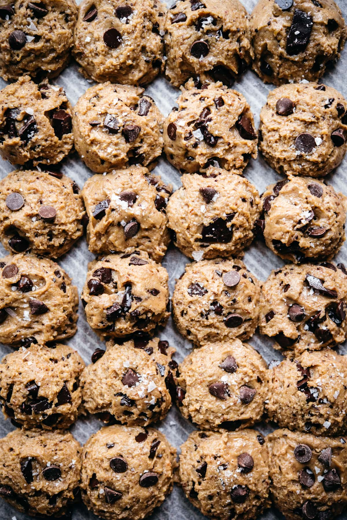 overhead view of vegan and gluten free chocolate chip cookies dough balls on parchment paper.