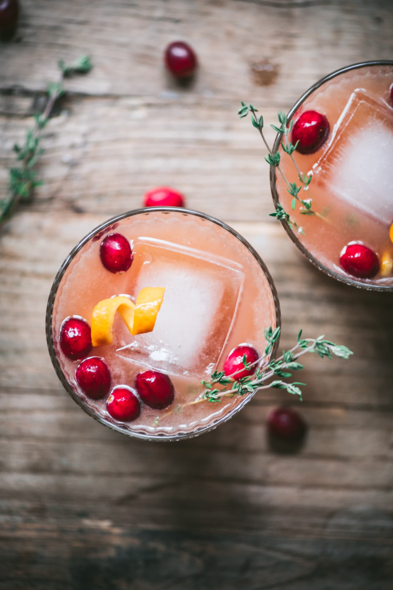 Close up of cranberry orange cocktails garnished with fresh thyme.