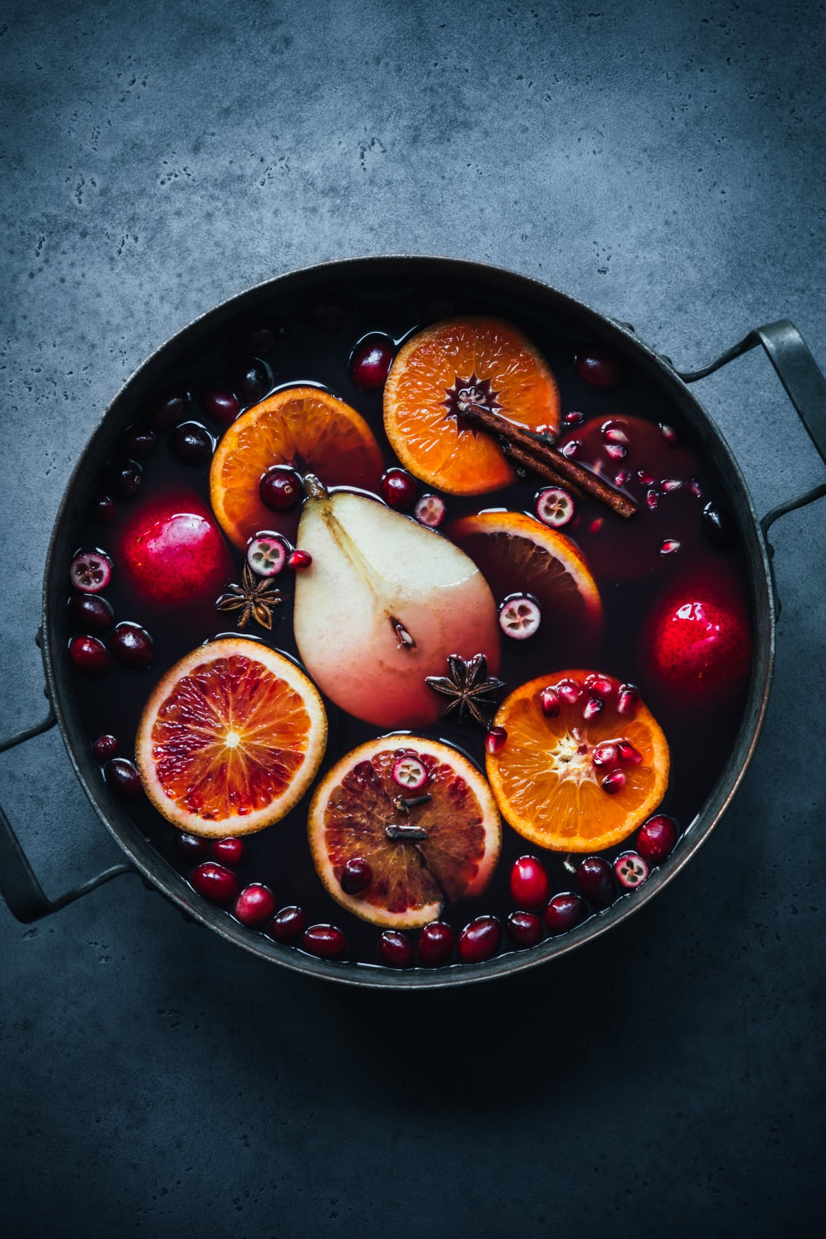 overhead view of spiced citrus and pear mulled wine in a large pot on blue backdrop.