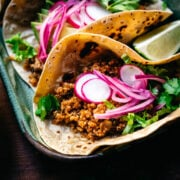 close up view of taco with vegan cauliflower quinoa taco meat and pickled onion.