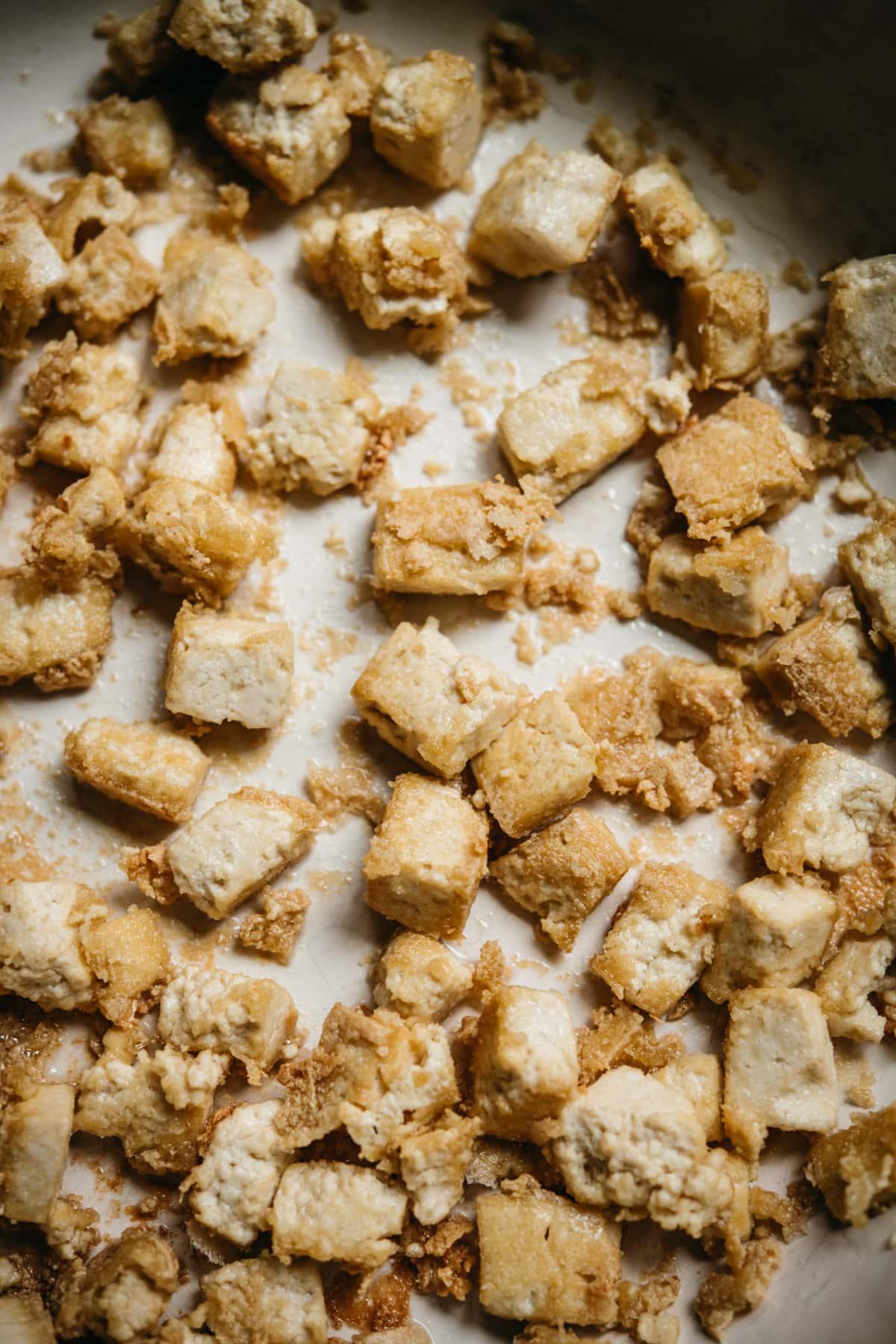 close up view of crispy pan-fried tofu in a pan.
