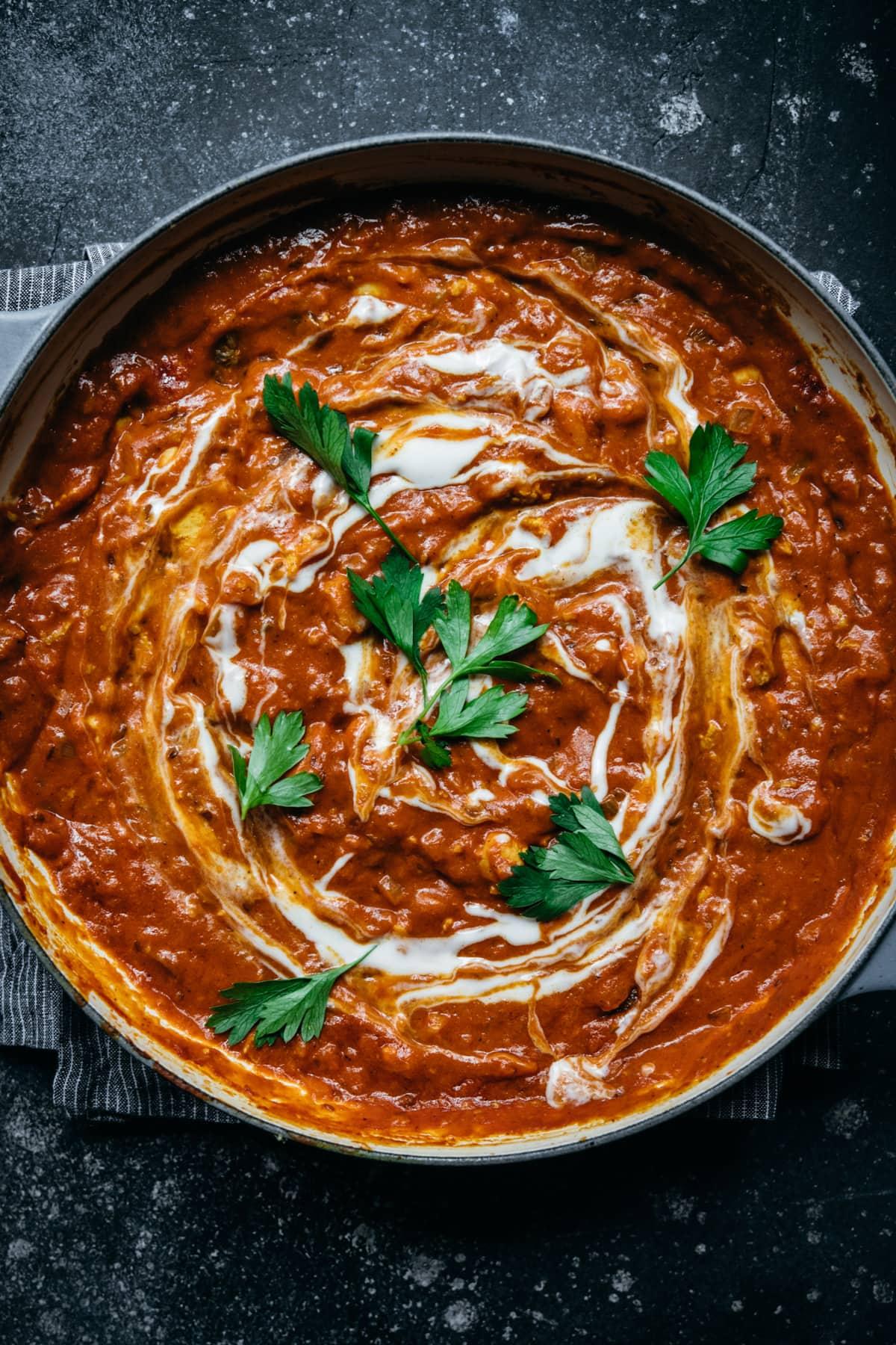 overhead view of vegan tofu tikka masala in a large pan with yogurt swirl and fresh herbs.