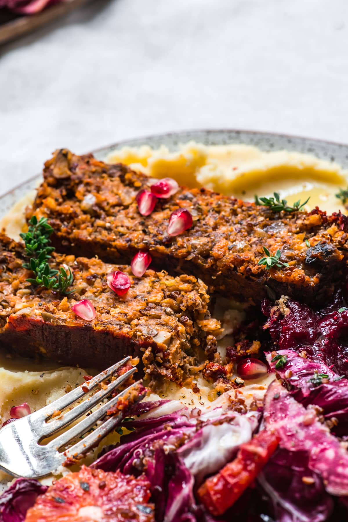 close up view of two slices of vegan lentil quinoa meatloaf on a plate.