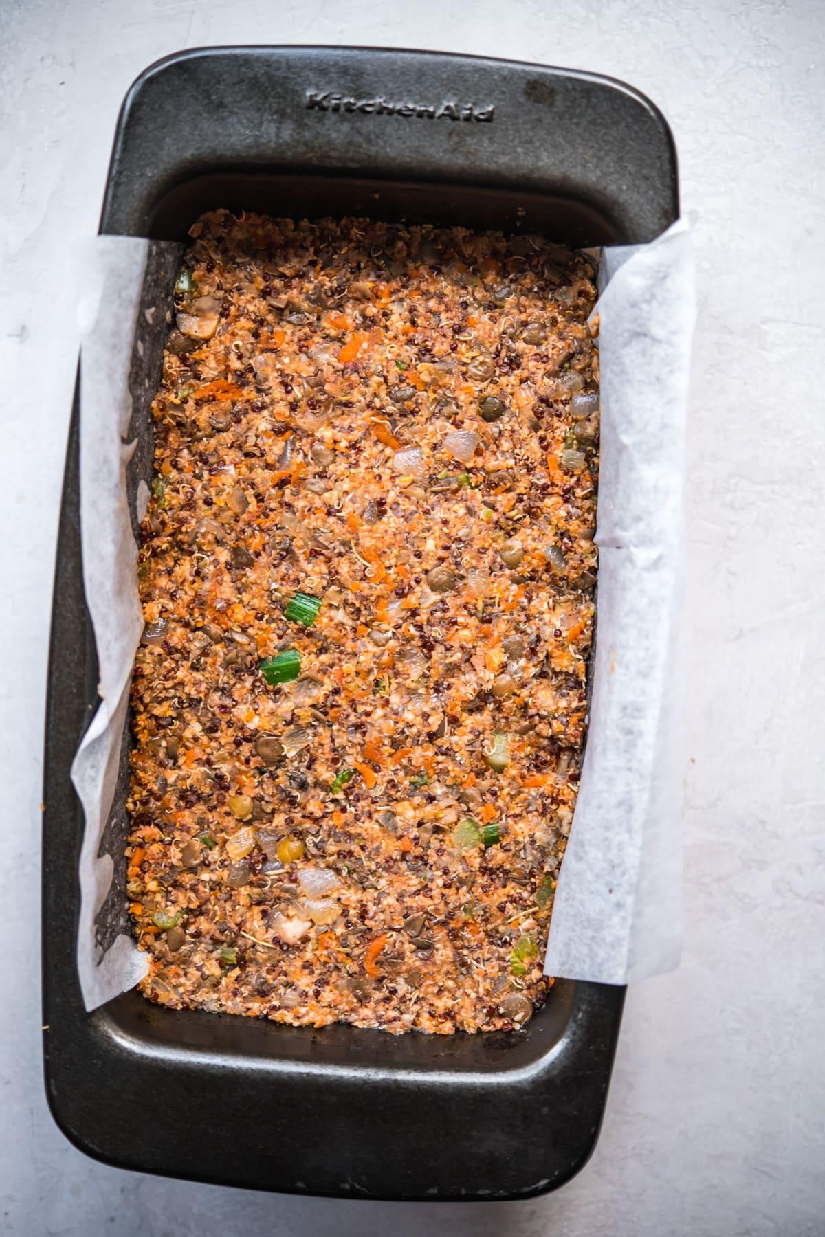 Vegan meatloaf pressed into a loaf pan before baking.
